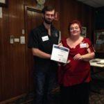 Fiona Hartnett, Mentor, presents a participation certificate.